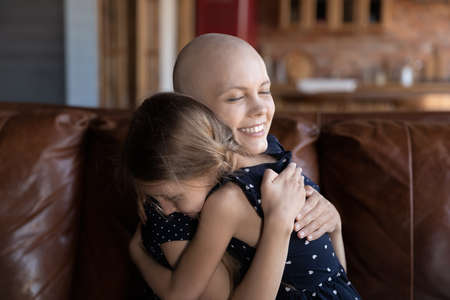 Smiling young ill cancer patient mother and little daughter embrace show love care support, happy Caucasian bald hairless sick mom and small girl child hug, feel grateful hopeful, healthcare concept