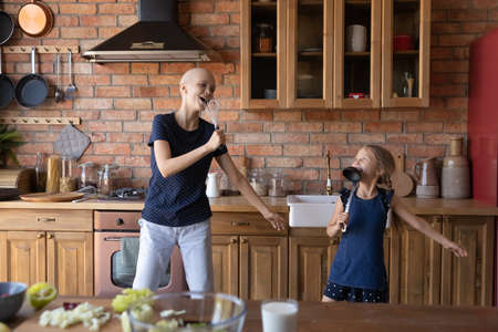 Happy young Caucasian sick cancer patient hairless bald mother feel playful sing in kitchen appliances with little daughter, smiling ill mom play have fun with small girl child on weekend at home