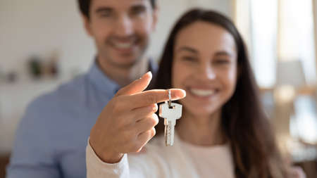 Close up young excited couple showing keys in hands to camera. Happy homeowners celebrating moving in new apartment or last banking mortgage payment, feeling glad of purchasing property, real estate. Banque d'images
