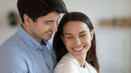 Close up head shot affectionate loving family couple newlyweds enjoying romantic sweet moment together indoors. Happy young devoted soulmates showing tender feelings, good relations concept.