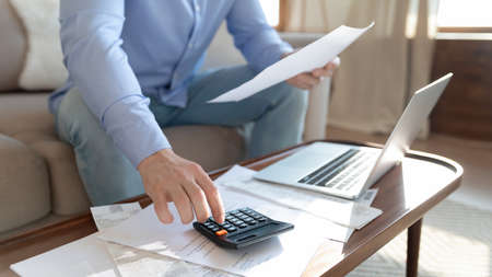 Close up young man holding paper bills, calculating monthly household expenditures alone at home, focused guy managing incomes and outcomes, paying taxes, considering financial paperwork indoors.