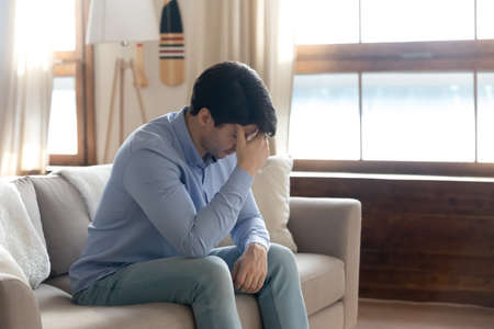Side view stressed young guy touching forehead, feeling unwell alone in living room. Depressed millennial handsome man thinking of life problems, worrying about betrayal relations breakup at home.