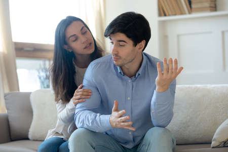 Loving young guilty woman trying making peace say sorry after misunderstanding or quarrel with angry offended stubborn man, sitting together on sofa at home, family relations crisis problems concept. Standard-Bild