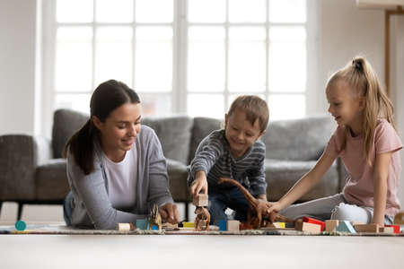 Caring young nanny spending daytime with laughing little children, playing with favorite toys, constructing buildings with cubes. Affectionate mother enjoying having fun with small daughter and som.