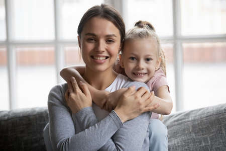 Cute little girl cuddling smiling beautiful young mother, sitting together on sofa, looking at camera. Portrait of affectionate millennial woman posing for photo with adorable preschool daughter. Standard-Bild