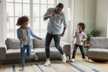 Playful young african American dad dancing playing in living room with two little children, happy biracial father have fun dancing with small kids son and daughter, enjoy weekend at home together Standard-Bild