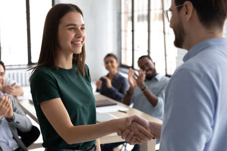 Close up executive shaking successful businesswoman hand at meeting, diverse colleagues applauding, team leader thanking worker for good work result, achievement, congratulating with promotion