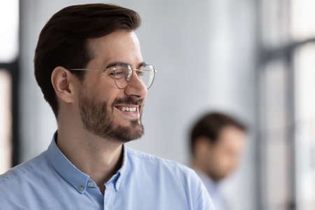 Close up profile smiling successful businessman wearing glasses looking to aside, business vision concept, overjoyed executive company owner dreaming, pondering project strategy or startup idea