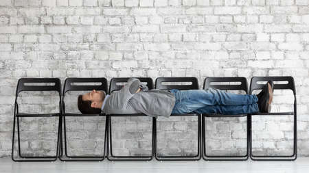 Bored exhausted candidate applicant businessman with arms crossed lying on office chairs in empty office hall, job seeker waiting for interview too long, employment and recruitment process