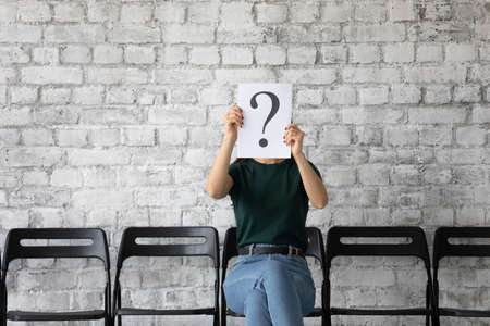 Young woman candidate hiding face behind sheet with question mark, sitting on chair in empty office hall, unemployed applicant seeker waiting for job interview, employment and hiring concept