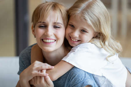 I love you so much. Portrait of happy young mother piggybacking cute smiling little daughter in living room, affectionate school age girl embracing beloved millennial female nanny or foster mom Imagens