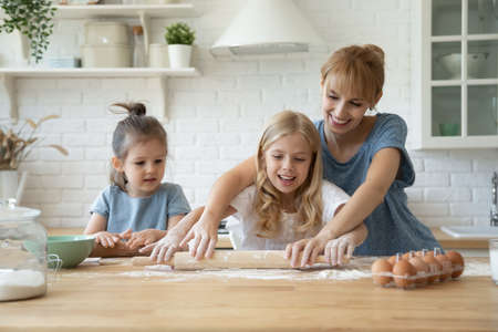Happy young mother showing elder daughter how to roll dough at kitchen table and younger girl funny clumsy little kid trying to repeat after sister, millennial babysitter teaching children to bake