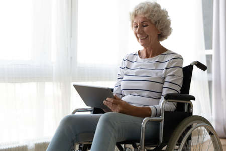 Happy old mature disabled woman sitting in invalid carriage, using computer tablet, enjoying communicating with friends online, watching funny movie or TV series indoors, handicapped people lifestyle.