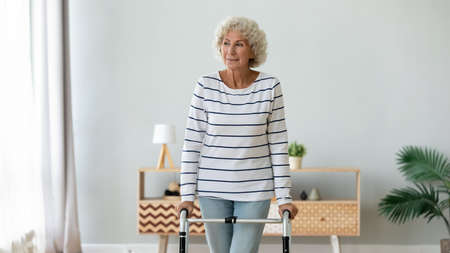 Happy middle aged senior hoary retired woman using walking frame, enjoying rehabilitation procedures indoors. Smiling older disabled grandmother making steps with walker, handicapped people lifestyle. Stock Photo