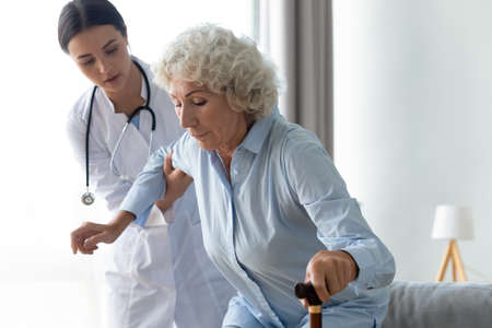 Careful young female physiotherapist helping older senior disabled patient get up from couch leaning on wooden stick. Middle aged retired woman using walking cane after injury, rehabilitation process.