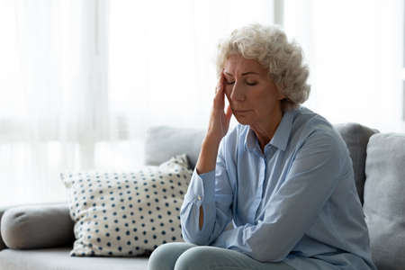 Exhausted mature old hoary woman sitting on sofa, suffering from headache indoors. Nervous middle aged elderly grandmother feeling doubtful about hard decision, health or psychological problems.