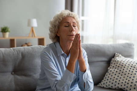 Peaceful middle aged woman sitting on sofa with folded in amen hands, feeling grateful indoors. Faithful senior mature praying God, asking for help, waiting for miracle or begging for forgiveness. Banco de Imagens