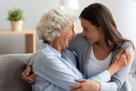 Overjoyed senior older hoary woman cuddling smiling pretty millennial grownup daughter, enjoying trustful conversation at home, laughing joking having fun while spending weekend time together.