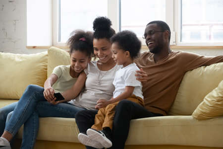 Mommy, daddy, look here. Happy african kid girl sitting on couch at home holding cellphone showing cute video to little preschool brother and smiling parents mom and dad, making call, using mobile app