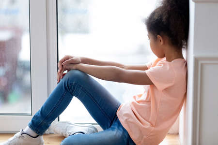 No one could understand me. Depressed lonely african teenage girl sitting on sill in her room hugging knee and sad looking at window, pensive black preteen young lady experiencing quarrel with parents Stock Photo
