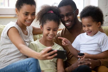 My sister looks funny on that photo. Happy black parents with two children elder daughter and toddler son communicating by cellphone using webcam, watching family pictures or video on sofa at home