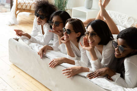 Funny diverse girls wearing stylish trendy sunglasses equal bathrobes lying in bed posing photographing in hotel bedroom. After spa procedures five women enjoy photoshoot celebrating hen-party concept