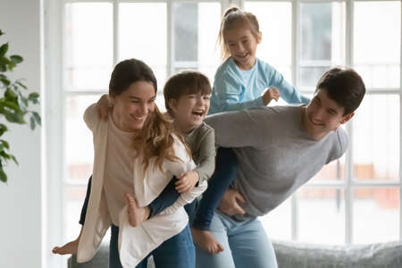 Playful young mixed race mother holding on back emotional little kid son while smiling father giving piggyback ride to happy preschool daughter, parents playing with energetic children at home.