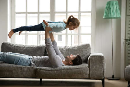 Happy lovely little kid girl flying on fathers straight arms, pretending to be plane. Smiling young daddy playing with cute small preschool child daughter, having fun on sofa in living room.