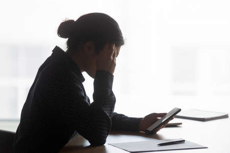 Side view stressed young indian ethnicity businesswoman looking at phone screen, confused about getting sms with bad news. Unhappy mixed race woman having problems with electronic device in office. Stock Photo