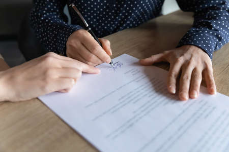 Close up young indian woman putting signature on hiring contract, multiracial female client satisfied with agreement terms of conditions, signing paper document at business meeting in office.