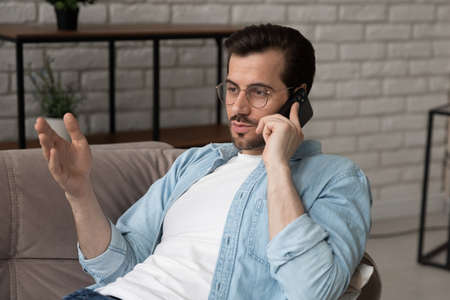 Millennial man in glasses sit on sofa at home have cellphone conversation or call using mobile provider wireless internet network connection, young Caucasian male speak talk on smartphone gadget