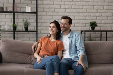 Happy young couple sit relax on sofa at home look in distance dreaming planning future together, smiling millennial man and woman renters tenants rest on couch hug embrace thinking visualizing