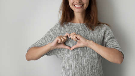 Crop close up of smiling young woman isolated on grey studio background show heart love gesture sign, happy millennial girl fell grateful thankful, volunteer or donate, donation, gratitude concept