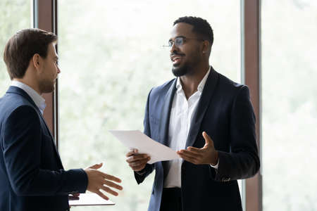 Positive african banker, consultant or finansial advisor convinsing caucasian customer in benefits of deal or bargain, confident black manager negotiating with european client or business partner