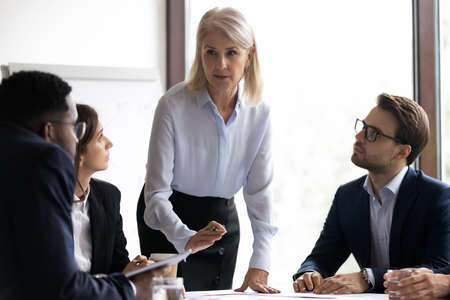 Senior female business coach or teacher speaking on corporate training before diverse team of managers or employees, elder woman mentor or experienced officer leading staff meeting or workshop