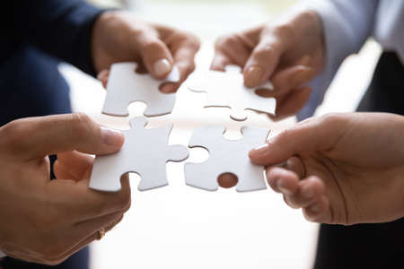 Close up of group of employees colleagues of different age and gender holding pieces of puzzle in hands and uniting them into a single whole. Teambuilding, successful teamwork, mutual support and help