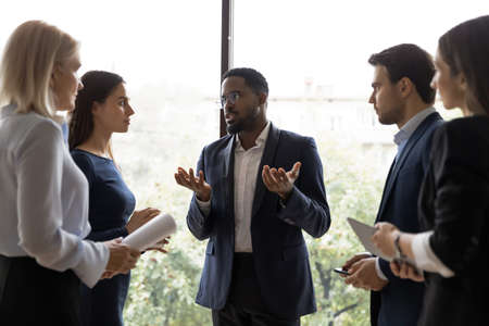 Focused black team leader giving brief instructions to diverse executives or employees during short break in office work, serious african enterpreneur talking to business partners at informal meeting