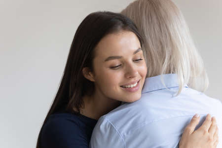 I am so happy to have you, mom. Adult woman hugging her elderly aged mother with care and tender gently touching her shoulder with chin, loving grown-up daughter holding on tight to her senior mom