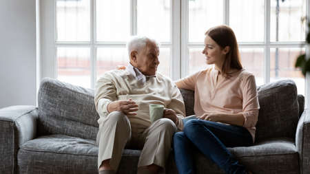 Smiling senior 80s man relaxing on sofa, talking to grown up daughter in living room. Happy different generations family enjoying drinking morning coffee with pleasant conversation together indoors.