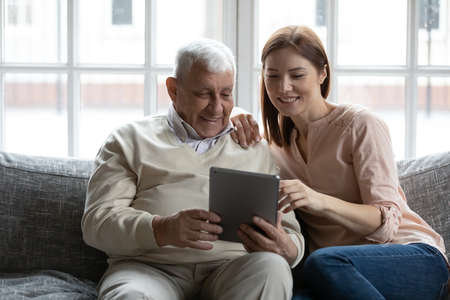 Smiling older mature male retiree showing funny photos on digital computer tablet to affectionate caring grown daughter, relaxing together on couch indoors, different generations hobby pastime.