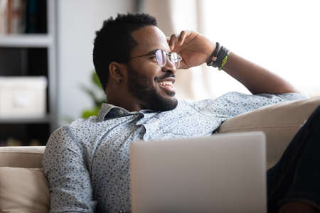 Close up positive African American man wearing glasses dreaming about good future or new opportunities, smiling freelancer or student relaxing with laptop on cozy couch, looking to aside at window Banque d'images