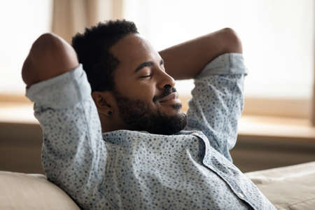 Close up peaceful satisfied African American man relaxing on cozy couch, daydreaming with closed eyes, napping, calm mindful young guy stretching, leaning back, meditating on sofa at home Stockfoto
