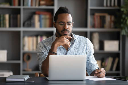 Thoughtful African American businessman looking at laptop screen, touching chin, pondering project plan or strategy, creative ideas, freelancer working online, sitting at desk in modern cabinet