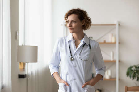 Dreamy young woman doctor wearing white uniform with stethoscope looking to aside at window, visualizing, pensive therapist physician gp lost in thoughts, pondering future, standing in hospital