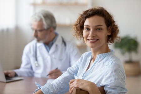 Head shot portrait smiling woman visiting senior doctor at medical appointment in hospital, satisfied female patient looking at camera, mature physician gp sitting at work desk on background