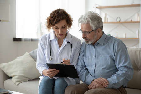 Young woman doctor nurse consulting mature patient during homecare visit, holding clipboard, filling card, illness history, therapist gp giving recommendations to senior man, sitting on couch at home
