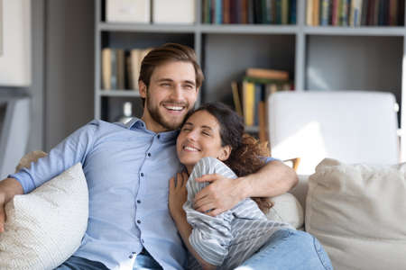 Happy young married couple embracing relaxing on sofa, enjoying sweet tender moment together at home. Smiling affectionate handsome man cuddling attractive woman, showing love feeling excited indoors.
