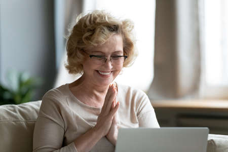 Smiling overjoyed mature woman wearing glasses reading good news, using computer, looking at laptop screen, watching video in social network, shopping online, received great shopping offer