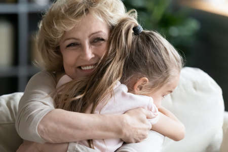 Close up smiling loving mature woman grandma hugging little granddaughter, happy grandmother and pretty girl enjoying tender moment, cuddling, spending leisure time together at home