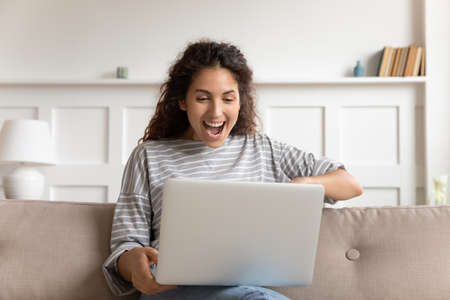 Excited woman sit on couch put computer on laps look at device screen read unbelievable offer, received new job incredible opportunity, gambling on-line auction winner. Cool apps, modern tech concept